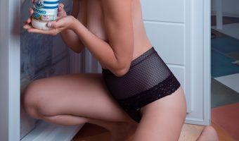 Naked girl opening a fridge