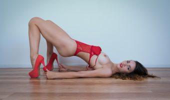 Girl lying on floor holding her high heels