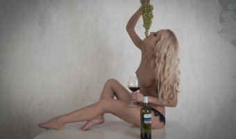 Girl sat on a table eating grapes and drinking red wine