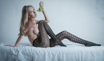 Girl in stockings lying on a bed eating grapes