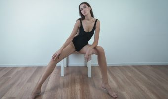 Tall woman in a black swimsuit sitting on a table