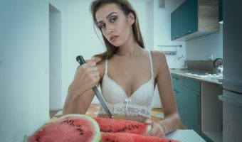 Woman wearing a bra slicing melons at a kitchen table