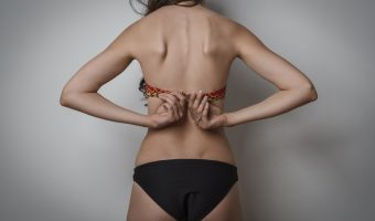 Girl unbuttoning her bra