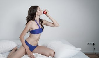 Woman in underwear on a bed eating an apple