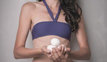 Girl in a bikini holding eggs