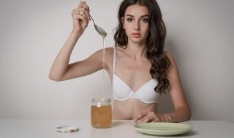Woman sat at a table wearing a bra and eating honey