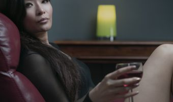 Photograph of model Kathryn Yip holding a glass of red wine