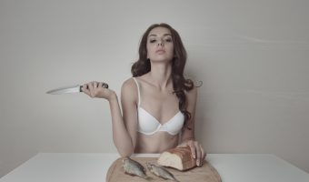 Woman in underwear sat at a table with fish and bread