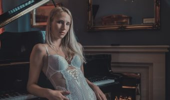 Photo of Bolton model Phoebe sitting at a grand piano
