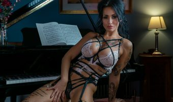 Photograph of a model sat at a piano in lingerie.