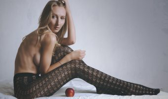 Model sitting on a bed wearing stockings.