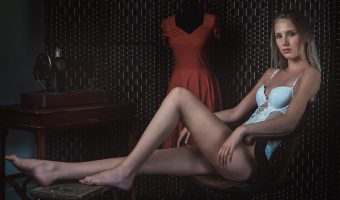 Beautiful model sat in a chair with a tailor's dummy.