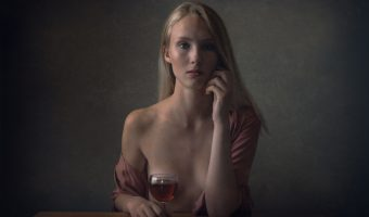 Model sat a table with a glass of wine.