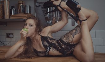 Model in lingerie eating an apple on a kitchen worktop