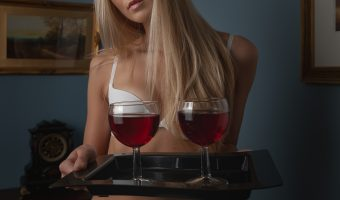 Model in lingerie holding a tray with glasses full of red wine
