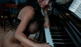 Beautiful female model playing a grand piano in lingerie