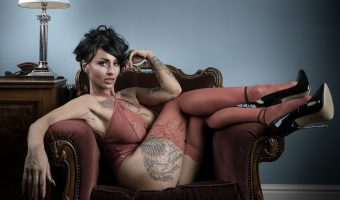Model sat on an antique chair wearing red lingerie