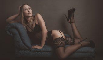 Female model in black lingerie sat on a chaise longue.