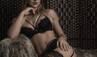 Photograph of a beautiful French model wearing lingerie and sitting on fur