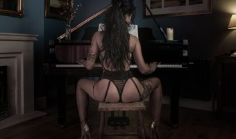 Photograph of a woman in black lingerie playing the grand piano