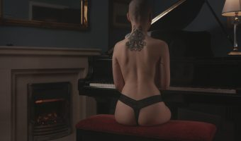 Photograph of a shaved headed female model sat at a grand piano
